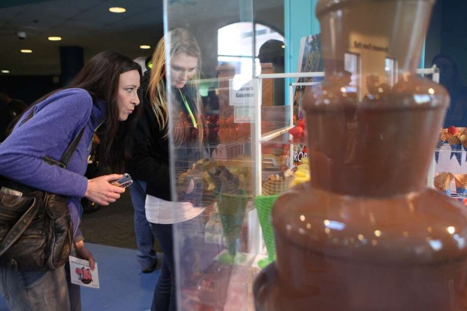 Allison Kamas, left, of Bridgeport, and Casandra Damato, of Oxford, watch a chocolate fountain, from Aurora Gourmet,  at the Chocolate World Expo at the Maritime Aquarium in Norwalk, Conn. on Sunday, Jan. 27, 2013. This year's expo is set for Jan. 26, 2014. Photo: BK Angeletti, B.K. Angeletti