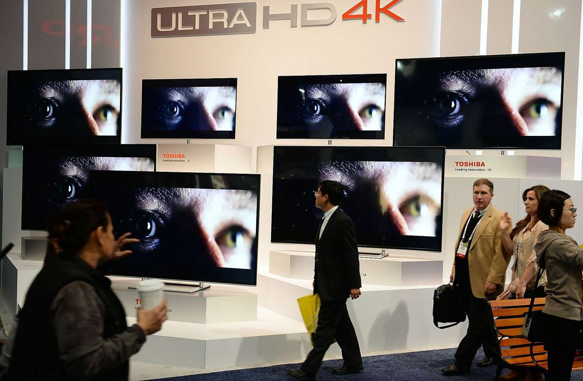 Attendees walk past the Toshiba Ultra HD 4K TV display at the 2014 International CES in Las Vegas, Nevada, January 8, 2014. The Consumer Electronics Show, one of the largest in the world, runs from Jan 7-10. AFP PHOTO / Robyn BeckROBYN BECK/AFP/Getty Images