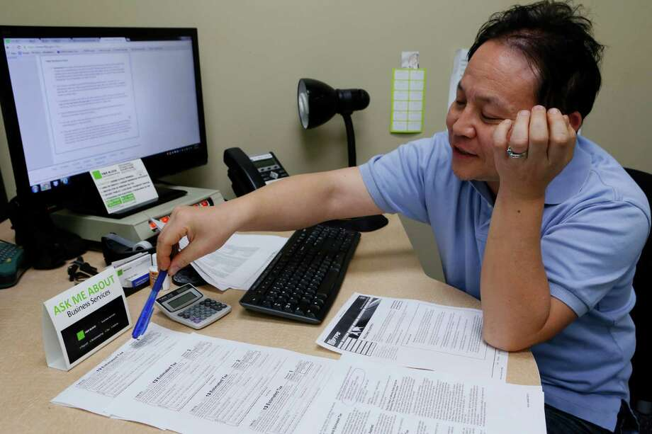 H & R Block public accountant John Lee explains how to file tax forms last year in Los Angeles. People will be able to start filing returns Friday. Photo: Damian Dovarganes, STF / AP