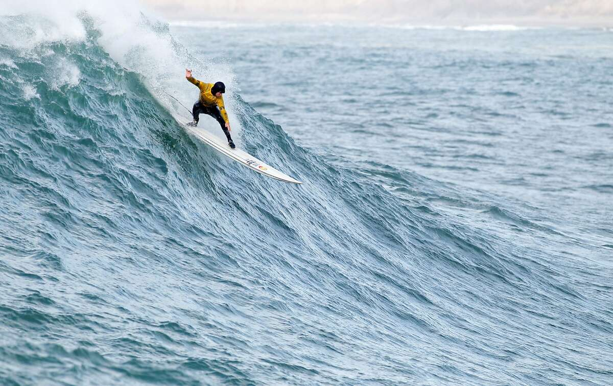 Grant Baker takes off on a wave during finals of the Maverick's Invitational surf contest in Half Moon Bay, Calif., on Friday, Jan. 24, 2014. Baker went on to win the event.