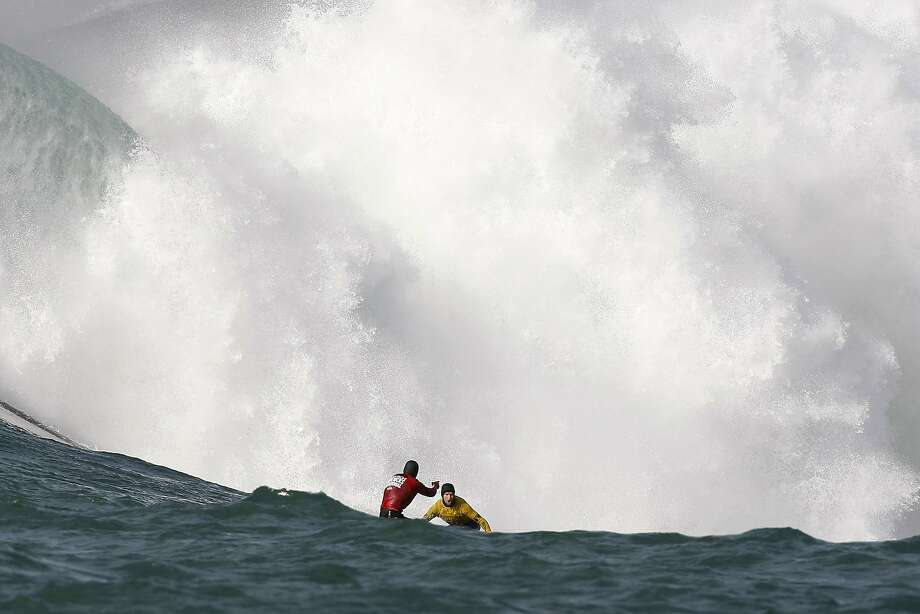 Tyler Fox, left, congratulates Grant Barker as they both ride out a wave  during the Finals of the 2014 Maverick's Invitational surf contest held in Half Moon Bay, CA, Friday, January 24, 2014. Photo: Michael Short, The Chronicle
