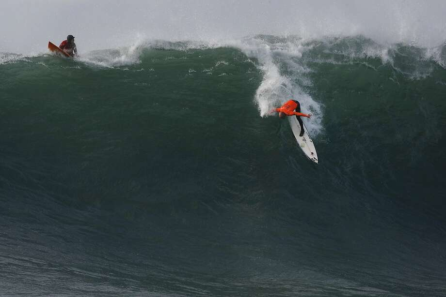 Tyler Fox, left, watches as Shane Dorian hangs on while dropping into a wave during the Finals of the 2014 Maverick's Invitational surf contest held in Half Moon Bay, CA, Friday, January 24, 2014. Photo: Michael Short, The Chronicle