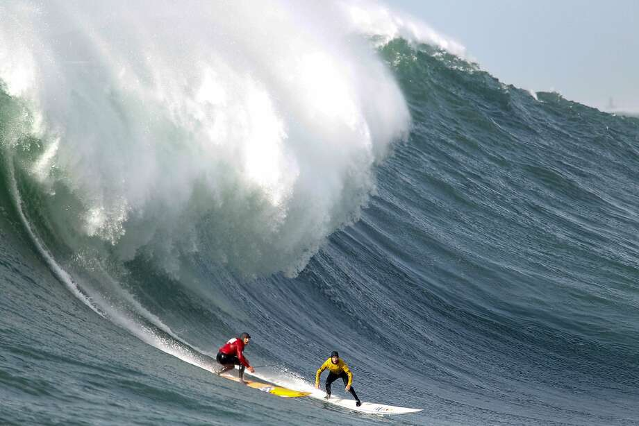 Grant Baker, yellow, and Tyler Fox take drop into the bottom of a wave during finals of the Maverick's Invitational surf contest in Half Moon Bay, Calif., on Friday, Jan. 24, 2014. Baker went on to win the event. Photo: Mathew Sumner, Special To The Chronicle