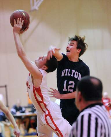 At left, Patrick Santini of Greenwich gets past Richie Williams (#12) of Wilton to score on a driving layup during the boys high school basketball game between Greenwich High School and Wilton High School at Greenwich, Firday night, Jan. 24, 2014. Photo: Bob Luckey / Greenwich Time