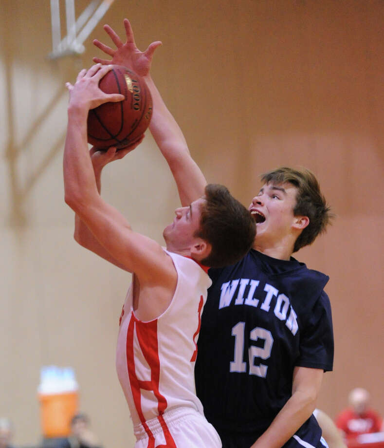 At left, Tommy Povinelli (#3) of Greenwich looks to pass while being defended by Wilton's Matt Shifrin (# 13) during the boys high school basketball game between Greenwich High School and Wilton High School at Greenwich, Firday night, Jan. 24, 2014. Photo: Bob Luckey / Greenwich Time