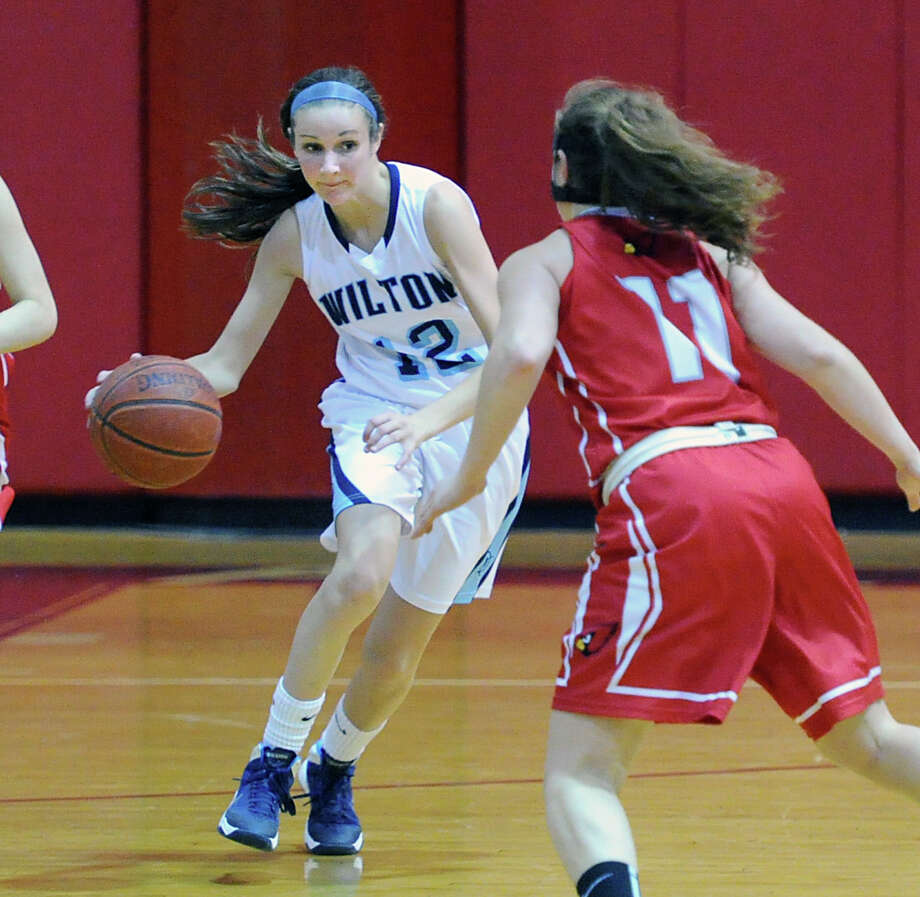 At left, Haley English (#12) of Wilton attempts to get past Alexa Moses (#11) of Greenwich during the girls high school basketball game between Greenwich High School and Wilton High School at Greenwich, Friday, Jan. 24, 2014. Wilton defeated Greenwich, 49-40. Photo: Bob Luckey / Greenwich Time