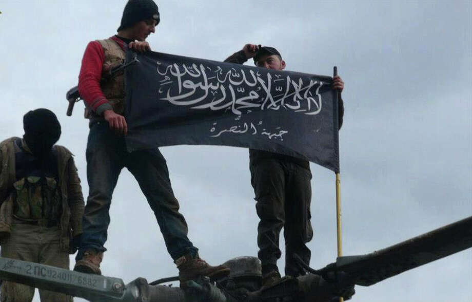 """FILE - In this Friday, Jan. 11, 2013 file citizen journalism image provided by Edlib News Network, ENN, which has been authenticated based on its contents and other AP reporting, rebels from al-Qaida affiliated Jabhat al-Nusra waving their brigade flag as they step on the top of a Syrian air force helicopter, at Taftanaz air base that was captured by the rebels, in Idlib province, northern Syria. Syria's uprising was not destined to be quick. Instead, the largely peaceful protest movement that spread across the nation slowly turned into an armed insurgency and eventually a full-blown civil war. More than 130,000 people have been killed, and more than 2 million more have fled the country. Nearly three years after the crisis began, Syria's government and opposition are set to meet in Geneva this week for the first direct talks aimed at ending the conflict. The Arabic words on the flag reads, """"There is no God only God and Mohamad his prophet, Jabhat al-Nusra."""" (AP Photo/Edlib News Network ENN, File) Photo: Anonymous, HOEP / EDLIB NEWS NETWORK ENN"""