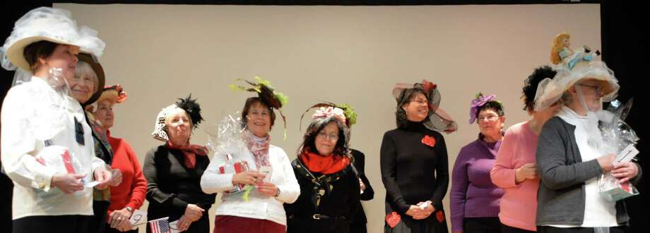 Women model the creative head wear they fashioned for the Mad Hatter Tea Party at the Westport Library on Friday. Photo: Jarret Liotta / Westport News contributed