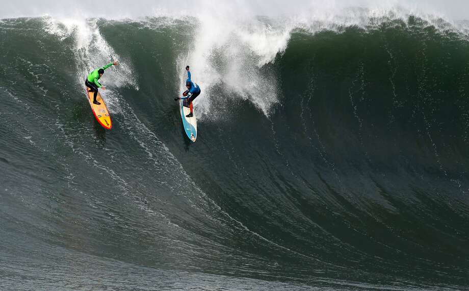 Danilo Couto, left, and Peter Mel share a wave during the first round of the Maverick's Invitational surf contest in Half Moon Bay, Calif., on Friday, Jan. 24, 2014. Photo: Mathew Sumner, Special To The Chronicle