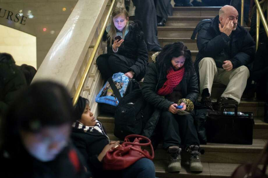 Commuters rest on the stairs of the main hall of Grand Central Station after a power problem with Metro-North Railroad's computer system caused the suspension of service on the Hudson, Harlem, and New Haven lines, Thursday, Jan. 23, 2014. Trains were brought to a halt for safety purposes while electricians worked to hook up temporary power to the computer system. Metro-North is the nation's second-busiest railroad and serves 281,000 riders a day in New York and Connecticut. (AP Photo/John Minchillo) ORG XMIT: NYJM205 Photo: John Minchillo / FR170537 AP