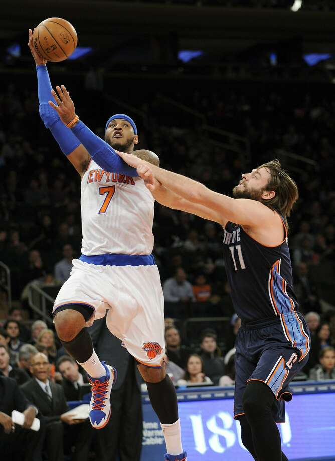 Carmelo Anthony evades Josh McRoberts on a record-setting night. Photo: Bill Kostroun, Associated Press