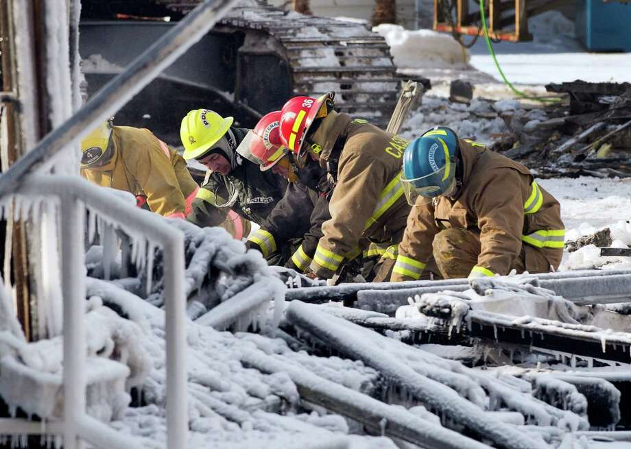 Rescue personnel search through the icy rubble of a fire that destroyed a seniors' residence Friday, Jan. 24, 2014, in L'Isle-Verte, Quebec. Five people are confirmed dead and 30 people are still missing, while with cause of Thursday morning's blaze is unclear police said. Authorities are using steam to melt the ice and to preserve any bodies that are buried. (AP Photo/The Canadian Press, Ryan Remiorz) ORG XMIT: RYR101 Photo: Ryan Remiorz / CP
