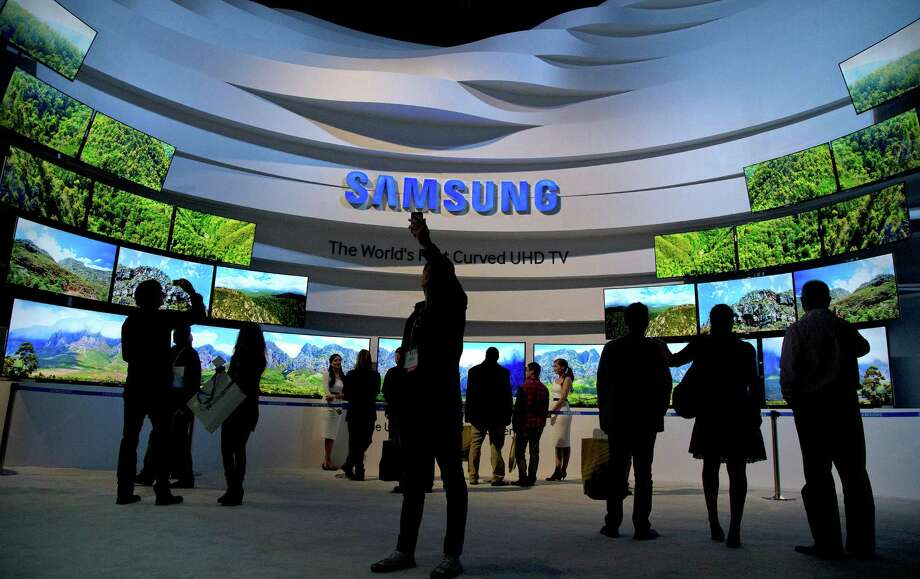 Visitors take in a display of Samsung's curved UHD TVs at the International CES in Las Vegas this month. Photo: Julie Jacobson, STF / AP