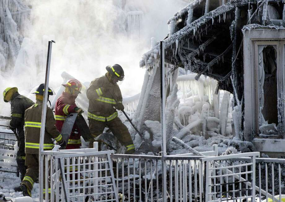 Rescue personnel search through icy rubble of fire that destroyed a seniors' residence  in L'Isle-Verte, Quebec. Eight people are confirmed dead and 30 people are still missing, police said. Authorities are using steam to melt the ice and to preserve any bodies that are buried. Photo: Ryan Remiorz / Associated Press / CP