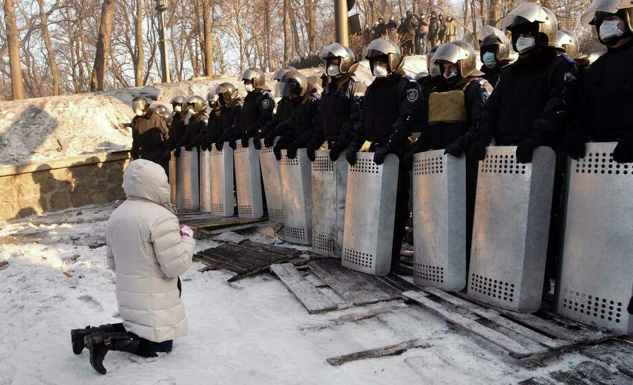 A woman kneels in front of riot police in Kiev, the center of clashes between protesters and Ukraine government forces. Demonstrations have spread to other parts of the country. Photo: Sergei Supinsky / AFP / Getty Images / AFP
