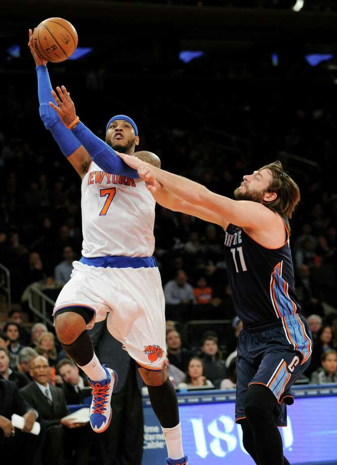 New York Knicks' Carmelo Anthony, left, puts up a shot as he gets by Charlotte Bobcats' Josh McRoberts during the first quarter of an NBA basketball game, Friday, Jan. 24, 2014, at Madison Square Garden in New York. (AP Photo/Bill Kostroun) ORG XMIT: NYBK103 Photo: Bill Kostroun / FR51951 AP