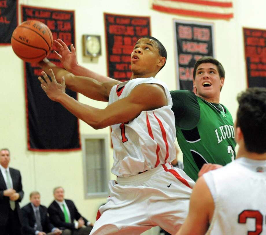 Academy's Ray Jerome, center, tries for the hoop and draws a foul from Bishop Ludden's Jack Rauch during their basketball game on Friday, Jan. 24, 2014, at Albany Academy in Albany, N.Y. (Cindy Schultz / Times Union) Photo: Cindy Schultz / 00025477A