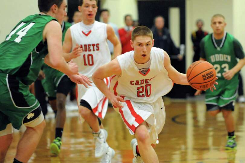 Academy's Matt Knezovic, center, drives up court during their basketball game against  Bishop Ludden