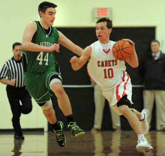 Academy's John Moutopoulos, center, drives up court as Bishop Ludden's Zach Walser defends during th