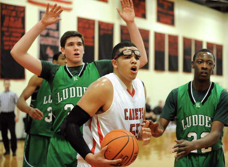 Academy's Marcus Jackson, center, questions an official's call during their basketball game against