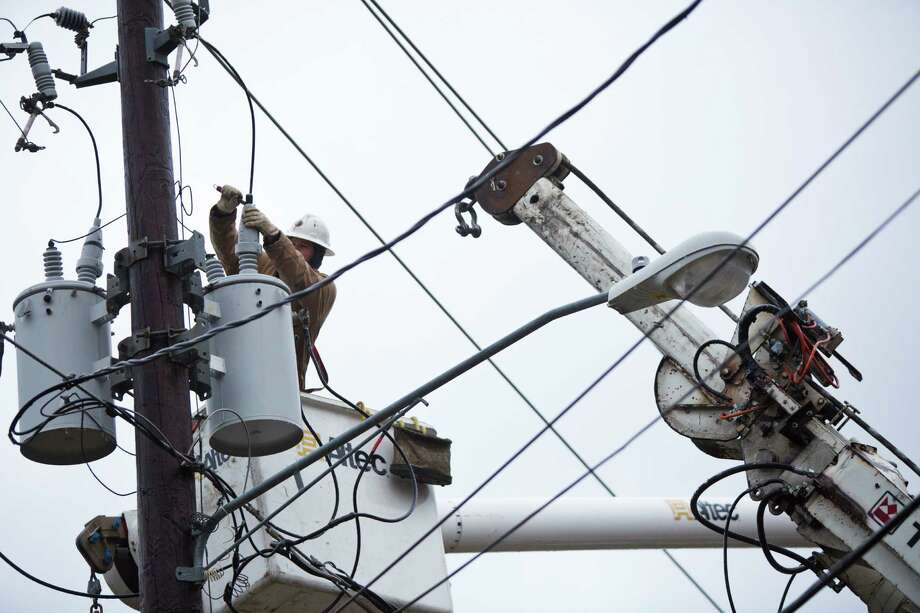 An electric brigade takes down a transformer damaged by the winter storm at Indiana Street, Friday, Jan. 24, 2014, in Houston. ( Marie D. De Jesus / Houston Chronicle ) Photo: Marie D. De Jesus, Staff / © 2014 Houston Chronicle