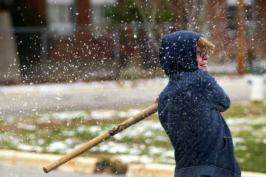 Billy Owen, of Lake Jackson, shatters a snowball after hitting it with a stick following an overnight snowfall Friday, Jan. 24, 2014, in Huntsville. ( Brett Coomer / Houston Chronicle ) Photo: Brett Coomer, Staff / © 2014 Houston Chronicle
