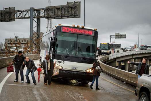Passengers of a Metro bus help each other to safely walk down the McKinney Street exit ramp off I-45 after being stranded. Photo: Michael Paulsen, Staff / © 2014 Houston Chronicle