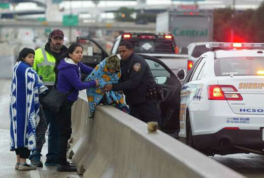 A police officer helps Janet Cortez, her daughter Leslie and son Aaron to the warmth of his car as they wait for a tow truck on U.S. 290. Photo: Johnny Hanson, Staff / © 2014  Houston Chronicle