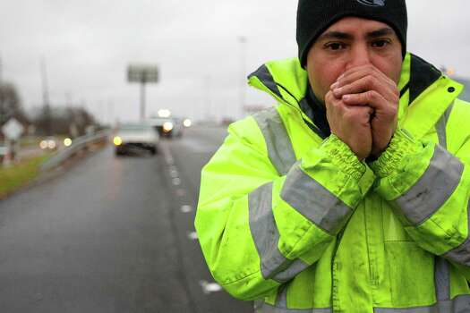 Tow truck driver Andy Mejia warms his hands as he waits to tow one of three vehicles involved in an early morning accident that snarled traffic on Highway 290 near Beltway 8. Photo: Johnny Hanson, Staff / © 2014  Houston Chronicle