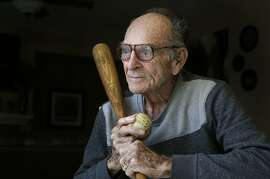 Former baseball player Neill Sheridan holds the very baseball and bat that he hit a 613 foot home run with back in 1953, as seen on Tuesday Jan. 21,  2014, at the home of his granddaughter in Antioch, Calif. Former professional  baseball player Neill Sheridan is credited with hitting the longest home run at the time back in 1953, a measured 613 feet.