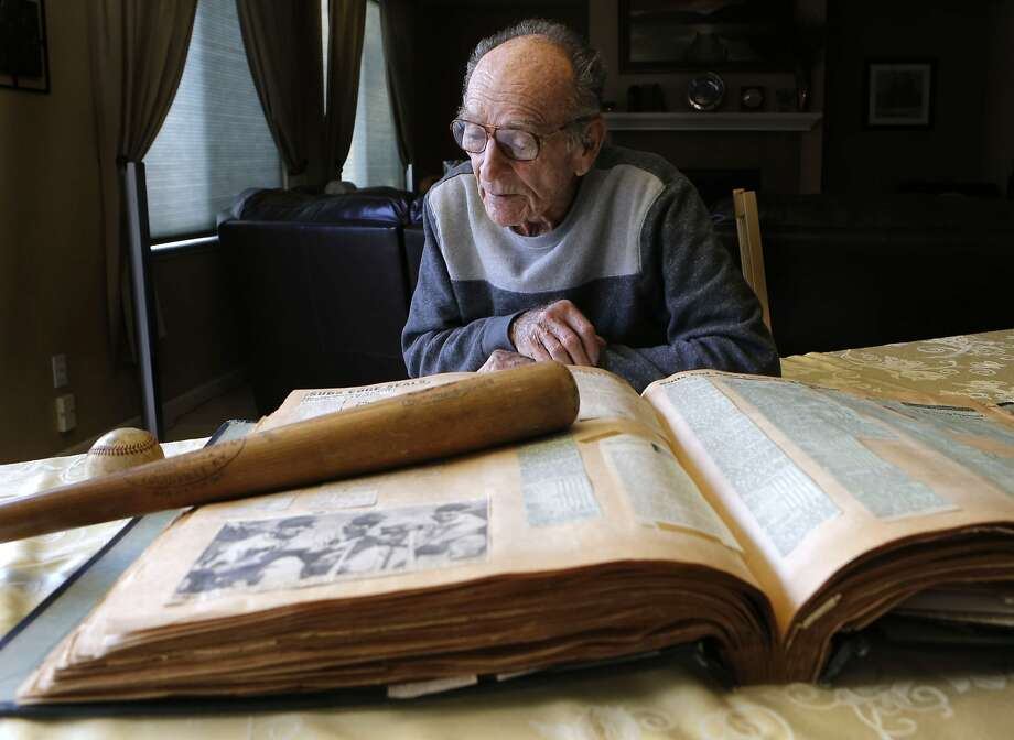 Former baseball player Neill Sheridan looks over collected memorabilia from long ago on Tuesday Jan. 21,  2014, at the home of his granddaughter in Antioch, Calif. Former professional  baseball player Neill Sheridan is credited with hitting the longest home run at the time back in 1953, a measured 613 feet. Photo: Michael Macor, The Chronicle