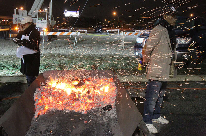Caroline Munoz (left) and Jesse Camarillo warm up by a fire in the parking lot of Cowboys Dancehall at the annual Cowboy Breakfast.