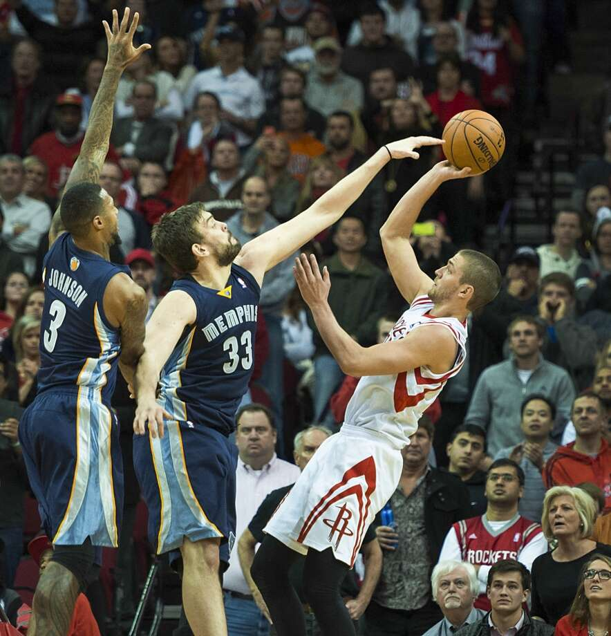 Rockets small forward Chandler Parsons (25) shoot over Grizzlies center Marc Gasol (33) and power forward James Johnson. Photo: Smiley N. Pool, Houston Chronicle