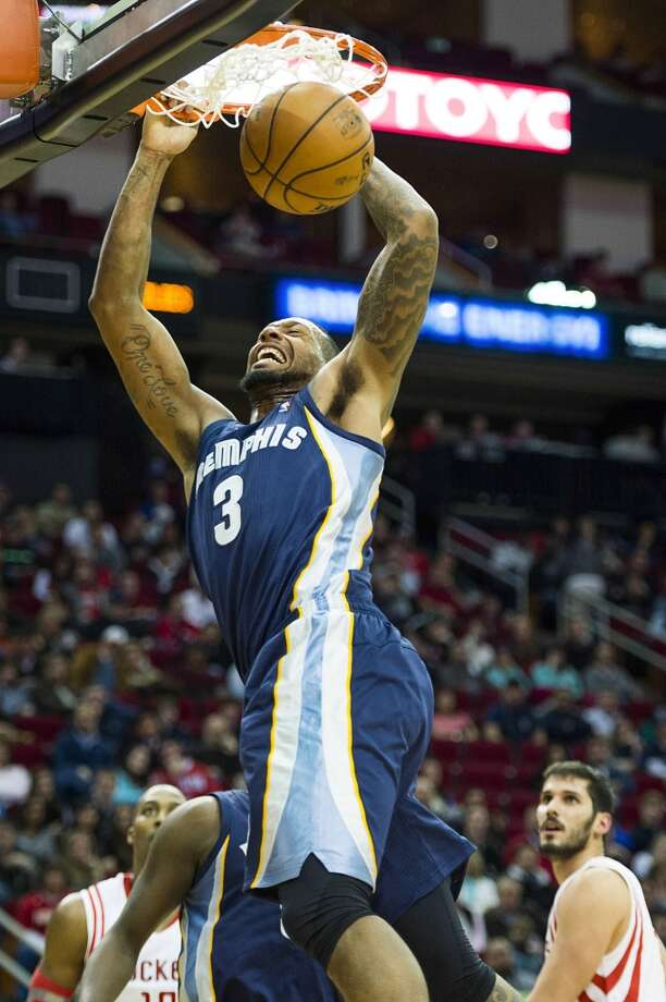 Grizzlies power forward James Johnson dunks the ball as Rockets center Dwight Howard and small forward Omri Casspi look on. Photo: Smiley N. Pool, Houston Chronicle