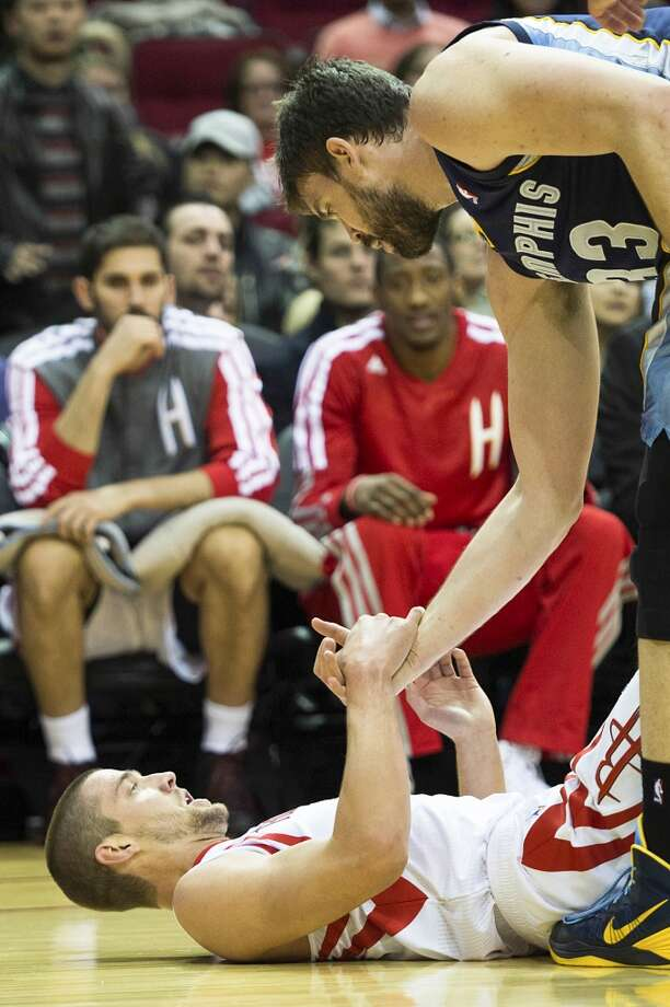 Rockets small forward Chandler Parsons gets a hand up from the floor by Grizzlies center Marc Gasol. Photo: Smiley N. Pool, Houston Chronicle
