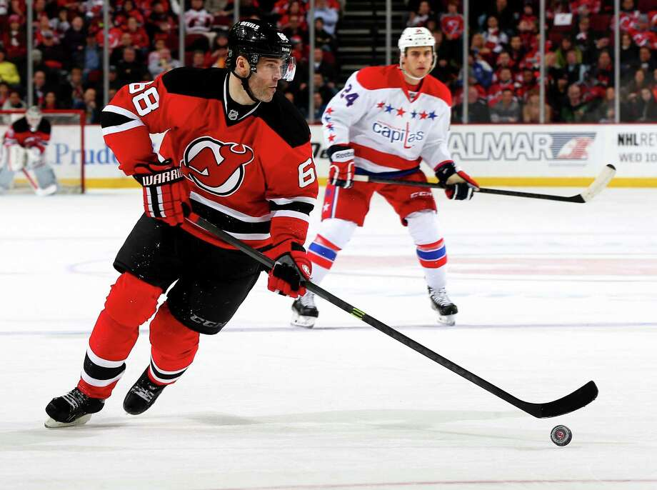 NEWARK, NJ - JANUARY 24:  Jaromir Jagr #68 of the New Jersey Devils takes the puck as Aaron Volpatti #24 of the Washington Capitals defends at Prudential Center on January 24, 2014  in Newark, New Jersey.  (Photo by Elsa/Getty Images) ORG XMIT: 181113596 Photo: Elsa / 2014 Getty Images