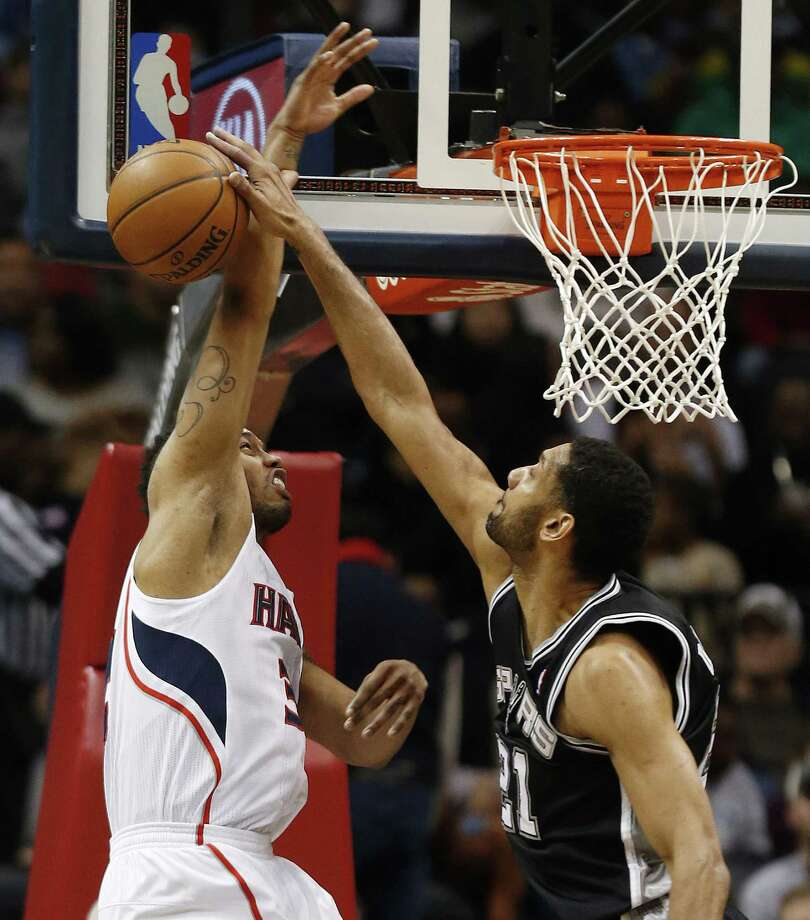 Besides his 17 points and 16 rebounds, Spurs big man Tim Duncan (right) had four blocks, including this one on Mike Scott. Photo: John Bazemore / Associated Press / AP