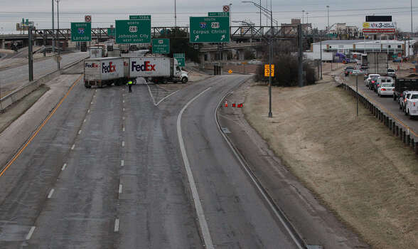 A FedEx truck blocks southbound Interstate 35 at Interstate 37. The Texas Department of Transportation covered roads with de-icer, but they still became slick. Photo: Photos By John Davenport / San Antonio Express-News / ©San Antonio Express-News/Photo may be sold to the public