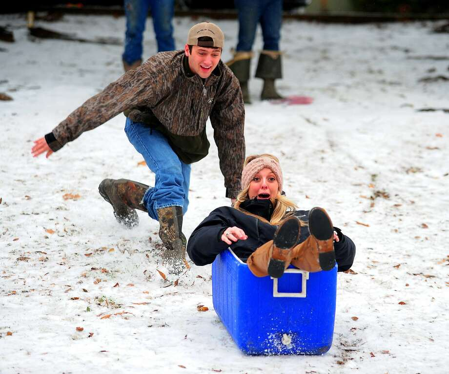 Ben Eggart, left, pushes Hannah Graham in an ice chest down a hill at Girard Park in Lafayette, La., Friday, Jan. 24, 2014. (AP Photo/The Daily Advertiser, Paul Kieu) Photo: Paul Kieu, Associated Press