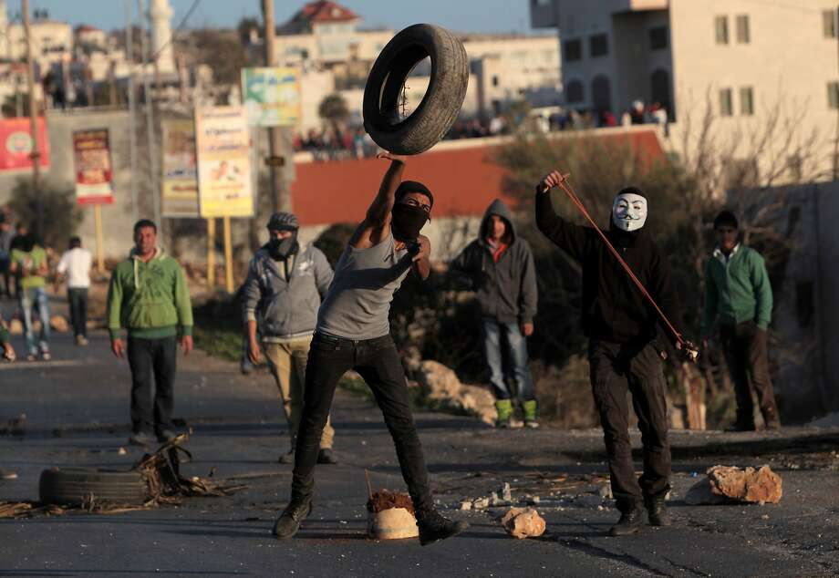 TOPSHOTS Palestinian stone throwers clash with Israeli security forces (unseen) in the West Bank village of Silwad, north of Ramallah, on January 24, 2014 following a protest of Palestinians against the expansion of the nearby Israeli settlement of Ofra. TOPSHOTS/AFP PHOTO / ABBAS MOMANIABBAS MOMANI/AFP/Getty Images Photo: Abbas Momani, AFP/Getty Images