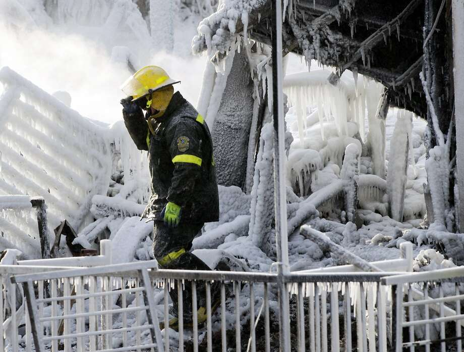 A police investigator walks through the icy rubble of a fire that destroyed a seniors' residence Friday, Jan. 24, 2014, in L'Isle-Verte, Quebec. Five people are confirmed dead and 30 people are still missing, while with cause of Thursday morning's blaze is unclear police said. Authorities are using steam to melt the ice and to preserve any bodies that are buried. (AP Photo/The Canadian Press, Ryan Remiorz) Photo: Ryan Remiorz, Associated Press