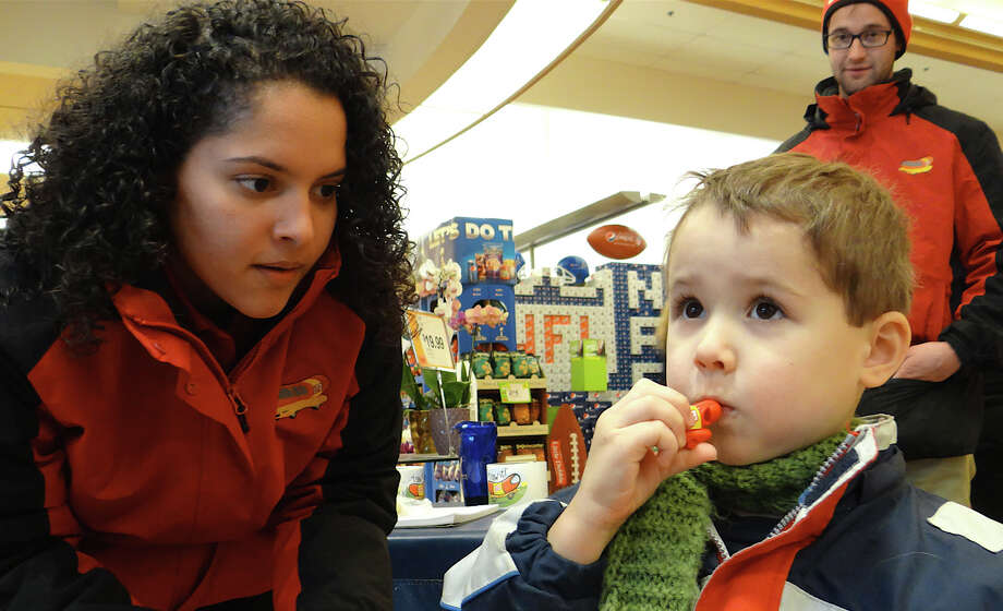 Oscar Mayer brand representatives Amanda Vazquez and Mike Tierney look on as Ryan Kavanaugh, 3, of Fairfield, toots a Wienie Whistle at Super Stop & Shop. Photo: Mike Lauterborn / Fairfield Citizen contributed