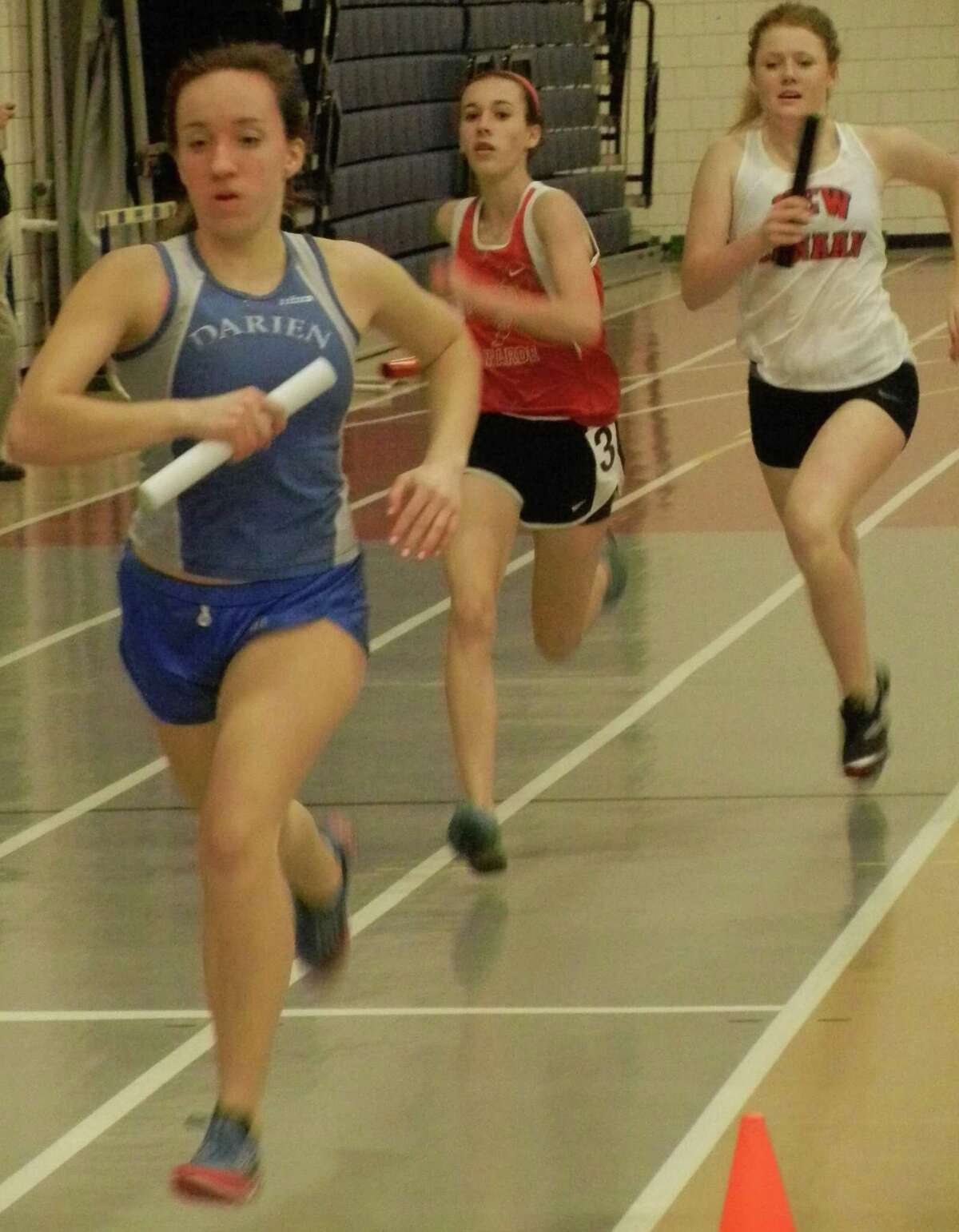 Fairfield Warde freshman Sarah Radziewicz, center, edging New Canaan's anchor-leg runner on Friday, Jan. 24 as the Mustangs won the 4-by-750-meter relay at the FCIAC East indoor track and field championship meet in Wilton. The Darien runner in front was beginning her last lap. Warde won this relay by 0.07 of a second.