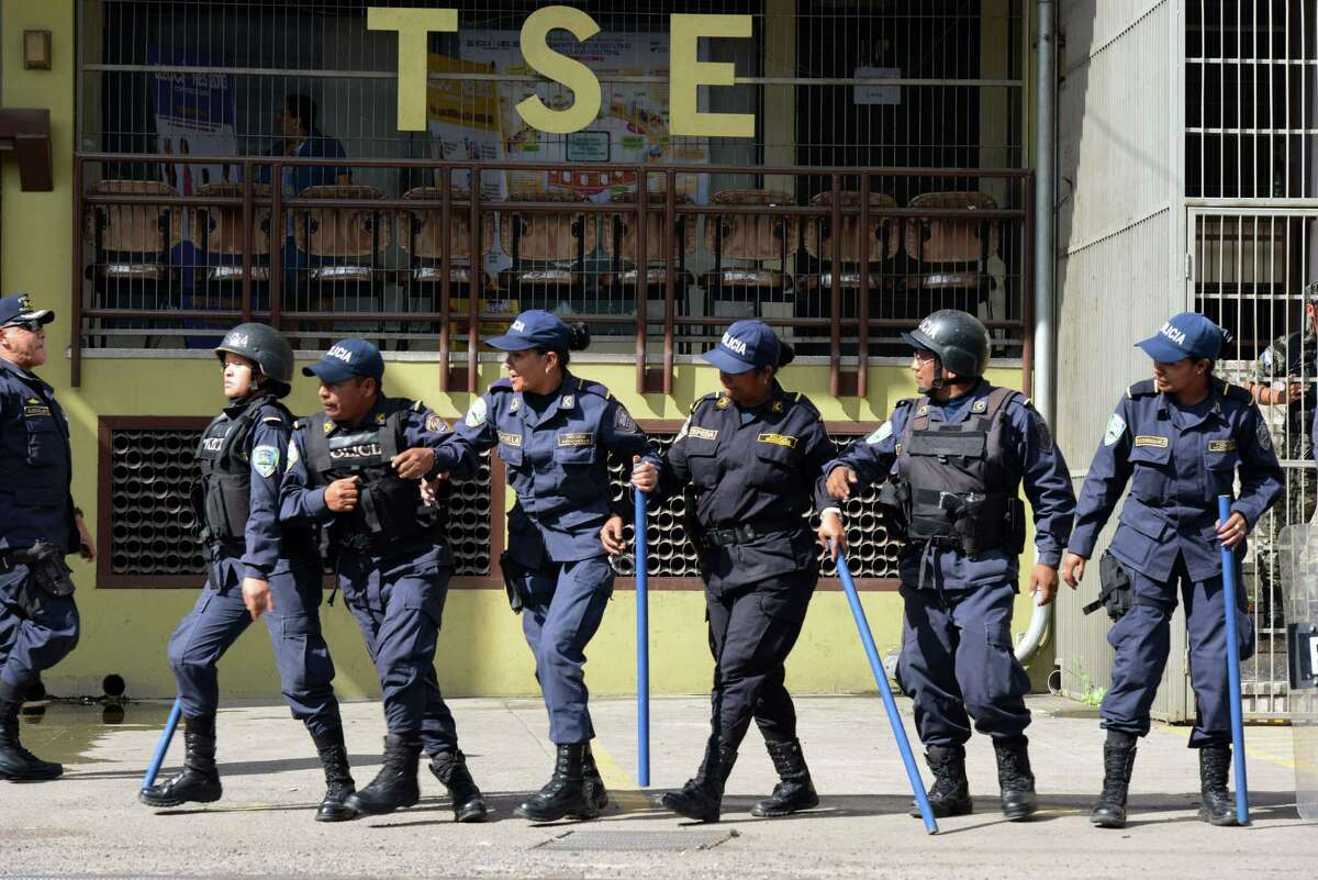 Police guard the building of the Supreme Electoral Tribunal during a protest the day after general elections in Tegucigalpa on Nov. 25. Political tension loomed over Honduras as the conservative candidate Juan Orlando Hernández led the early count in the elections while his leftist opponents claimed fraud.