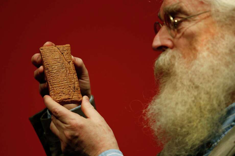 "Irving Finkel, curator in charge of cuneiform clay tablets at the British Museum, holds the 4,000-year-old clay tablet containing the story of a vast boat and the flood. He has written a new book: ""The Ark Before Noah."" Photo: Sang Tan, STR / AP"