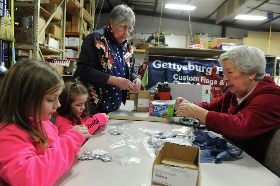 From left, Kaitlyn Farron, 6, and and her sister Sydney, 4, from Troy, Sue Wells and Marie Flavin of Troy work on stuffing stars and messages into small plastic bags at Gettysburg Flag Works Monday, Jan. 20, 2014 in East Greenbush, N.Y. Well leads a corps of Stars for Our Troops volunteers who wash, dry and remove embroidered stars from worn out flags. The women and men volunteers place the stars in small plastic bags with a message to troops that reads: OI am part of the American flag that was flown over a home in the U.S.A. I can no longer fly. In the sun and wind, I have become tattered and torn but not forgotten. Please carry me as a reminder that you are NOT forgotten.O (Lori Van Buren / Times Union) Photo: Lori Van Buren / 00025412A
