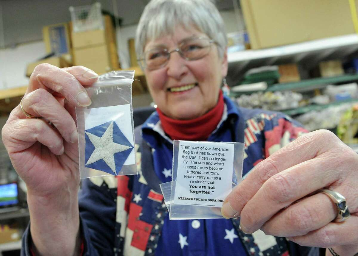 Sue Wells holds up a packets containing a flag star and a message to a vet or soldier at Gettysburg Flag Works Monday, Jan. 20, 2014 in East Greenbush, N.Y. Well leads a corps of Stars for Our Troops volunteers who wash, dry and remove embroidered stars from worn out flags. The women and men volunteers place the stars in small plastic bags with a message to troops that reads: OI am part of the American flag that was flown over a home in the U.S.A. I can no longer fly. In the sun and wind, I have become tattered and torn but not forgotten. Please carry me as a reminder that you are NOT forgotten.O (Lori Van Buren / Times Union)