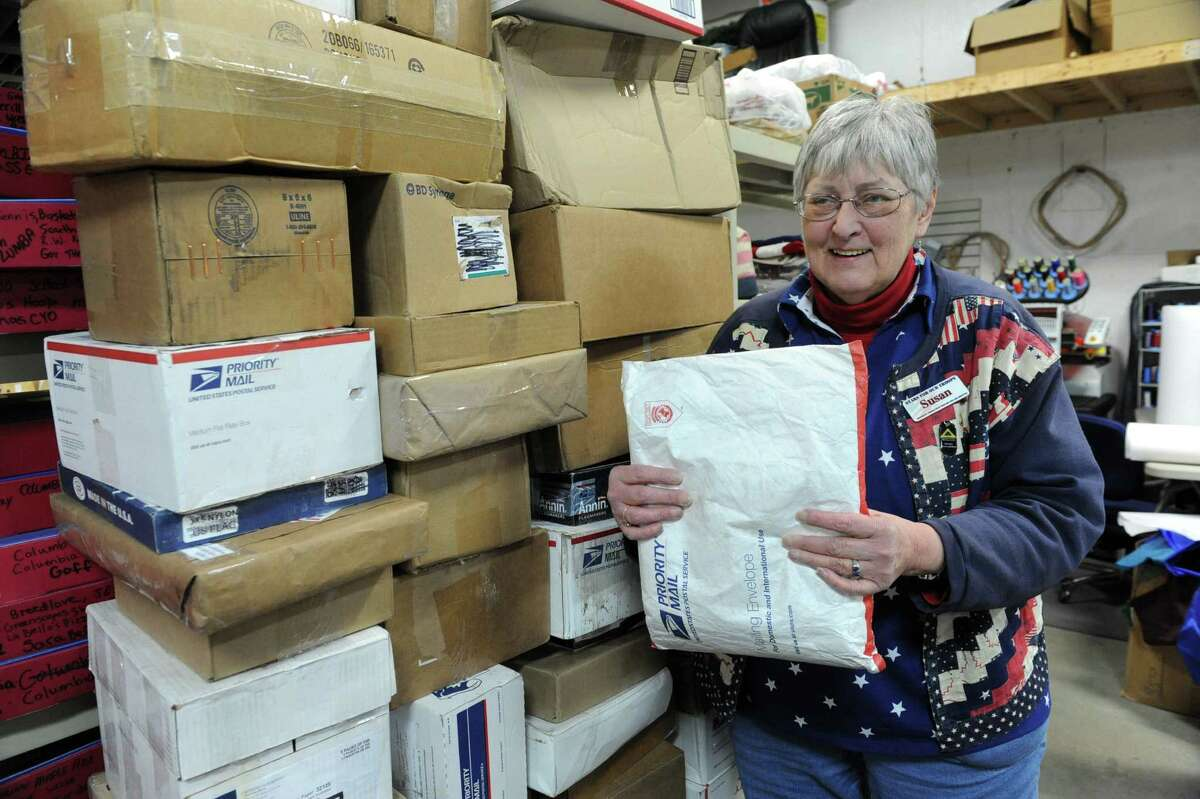 Sue Wells holds one of many envelopes containing donated small plastic bags as she stands next to boxes of donated worn out flags at Gettysburg Flag Works Monday, Jan. 20, 2014 in East Greenbush, N.Y. Well leads a corps of Stars for Our Troops volunteers who wash, dry and remove embroidered stars from worn out flags. The women and men volunteers place the stars in small plastic bags with a message to troops that reads: OI am part of the American flag that was flown over a home in the U.S.A. I can no longer fly. In the sun and wind, I have become tattered and torn but not forgotten. Please carry me as a reminder that you are NOT forgotten.O (Lori Van Buren / Times Union)