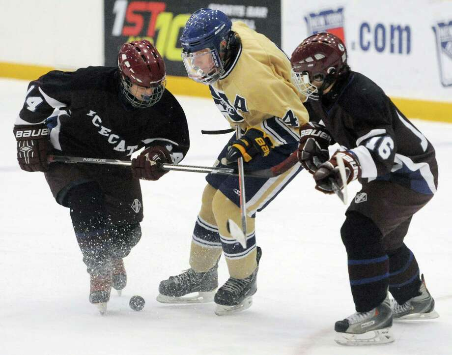 Newtown's Dan Harrison, center, battles for the puck Brookfield/Bethel/Danbury's Doug Alfidi, left, and Austin Natale in Newtown's 3-1 win over Brookfield/Bethel/Danbury in the high school hockey game at Danbury Arena in Danbury, Conn. on Saturday, Jan. 25, 2014. Photo: Tyler Sizemore / The News-Times