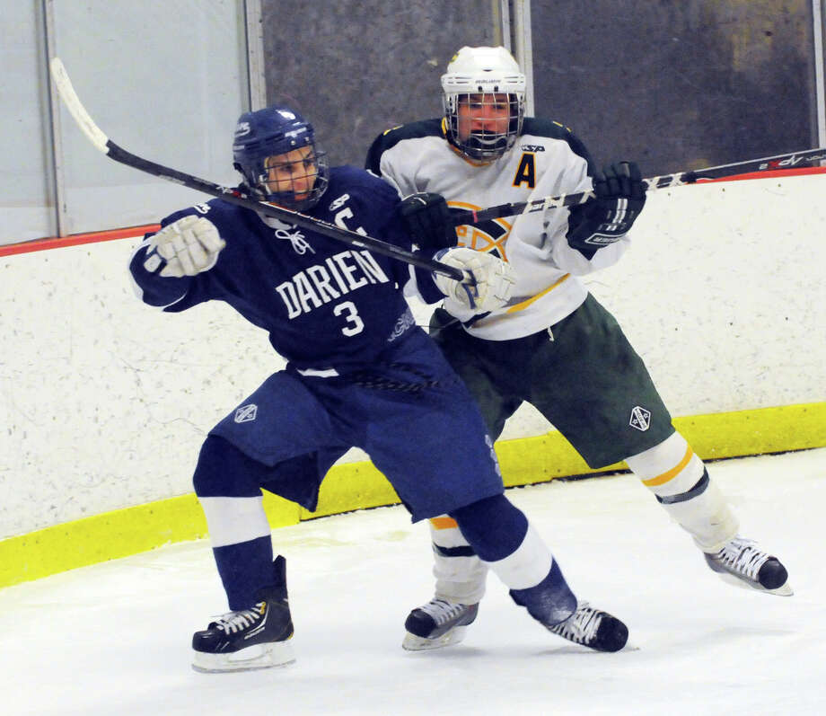 Darien's Thomas Watters and Trinity's Carmine DeRubeis in action as Darien and Trinity Catholic High Schools face off in a boys hockey game at Terry Conners Rink in Stamford, Conn., Jan. 25, 2014. Photo: Keelin Daly / Stamford Advocate Freelance